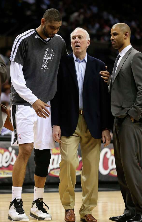 The Spurs\' Tim Duncan talks with coach Gregg Popovich as assistant coach Ime Udoka looks on during the first half against the Orlando Magic at the AT&T Center, Wednesday, April 3, 3013. Photo: Jerry Lara, San Antonio Express-News / ©2013 San Antonio Express-News