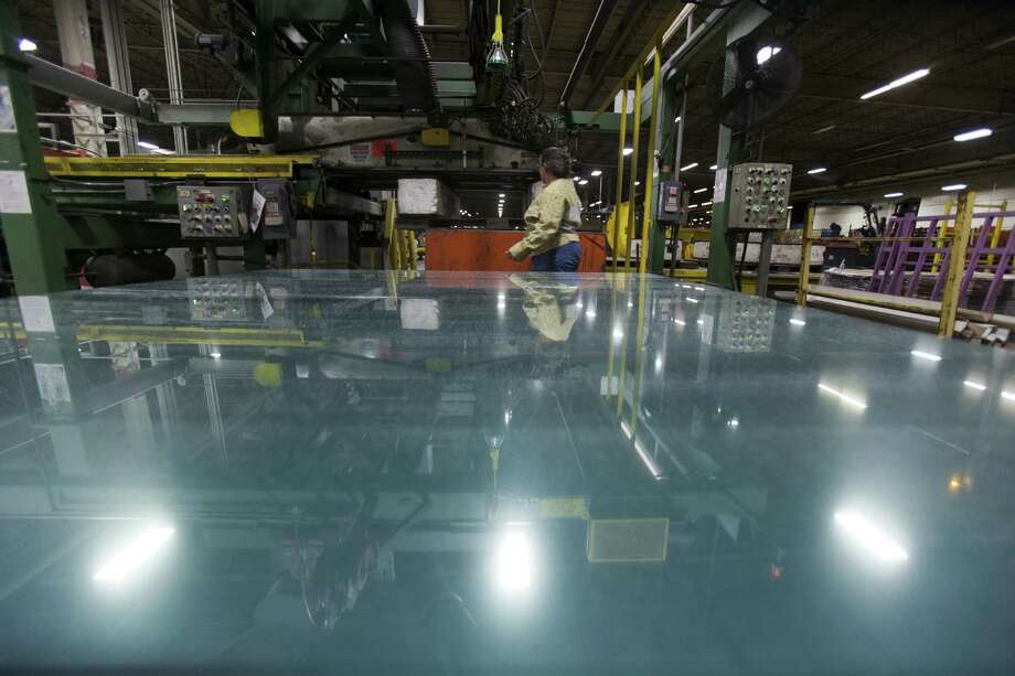 An employee walks past a sheet of glass at the PPG Industries glassmaking plant in Carlisle, Pa., which uses natural gas in its manufacturing. A predicted surge in factory employment because of a drop in natural gas prices has not materialized. Photo: Jessica Kourkounis / New York Times