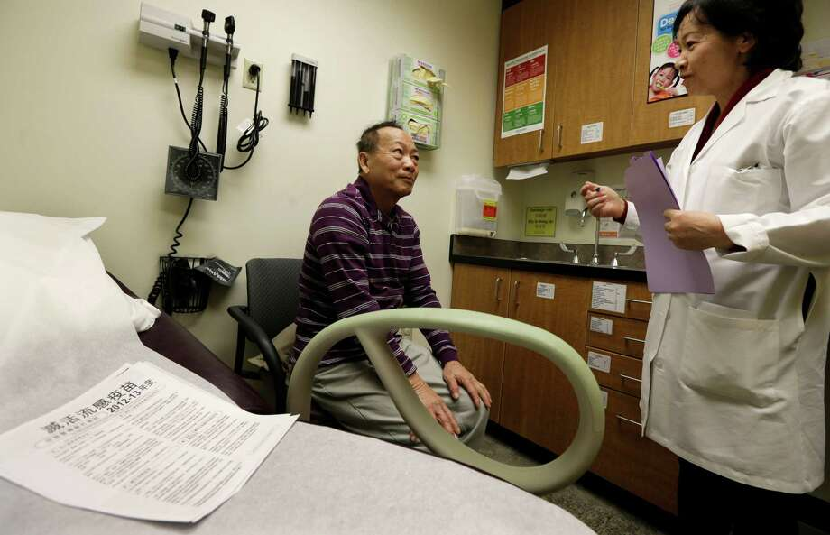 Chan Lai Ly speaks with Cecilia Trinh, a medical assistant, during a check-up in Seattle. U.S. service companies grew at a more cautious pace last month, while private employers eased up on hiring, reports indicate. Photo: Ted S. Warren, STF / AP