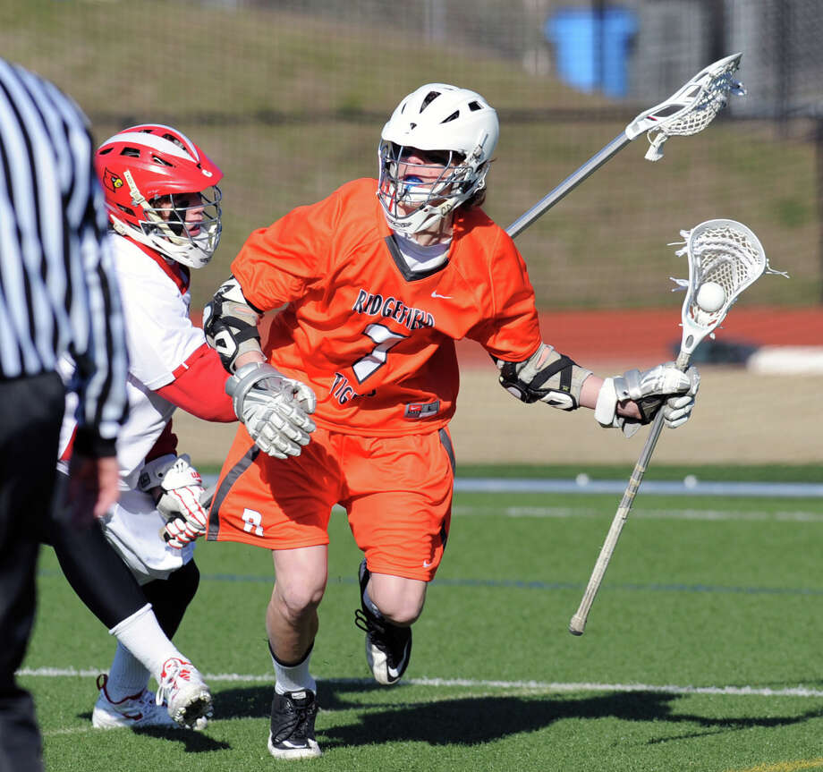At right, Simon Mathias # 7 of Ridgefield gets past a Greenwich defender during the boys high school lacrosse match between Greenwich High School and Ridgefield High School at Greenwich, Wednesday, April 3, 2013. Ridgefield won the match over Greenwich by a score of 10-5. Photo: Bob Luckey / Greenwich Time