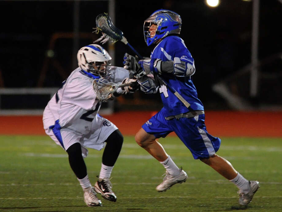 Fairfield Ludlowe's #22 Matthew Montanez, left, works to slow down Darien player #14 Kyle Cornell, during boys lacrosse action in Fairfield, Conn. on Wednesday April 3, 2013. Photo: Christian Abraham / Connecticut Post