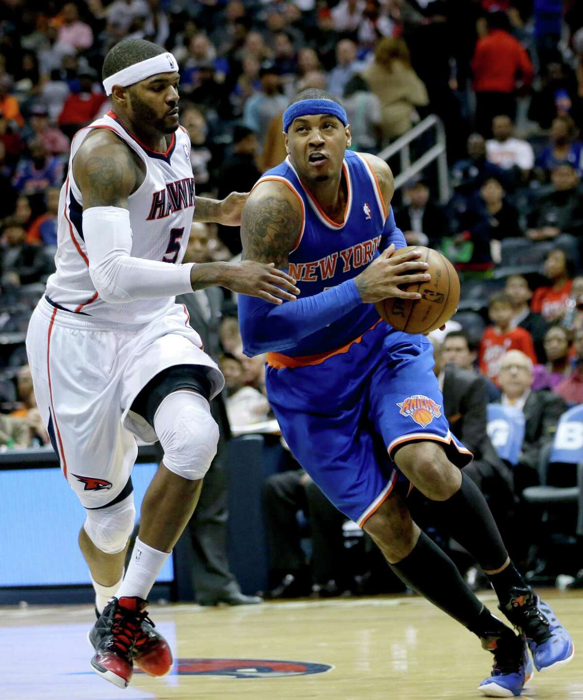 New York Knicks' Carmelo Anthony, right, drives to the hoop against the defense of Atlanta Hawks' Josh Smith in the fourth quarter of an NBA basketball game, Wednesday, April 3, 2013, in Atlanta. New York won 95-82. (AP Photo/David Goldman)