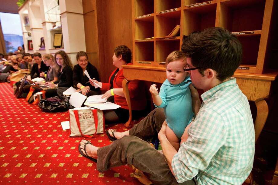 Zack Turpin, a teaching fellow at the University of Houston, plays with his 10-month-old son, Jack, during a Wednesday sit-in in the lobby of President Renu Khator's office. Teaching fellows from the Creative Writing Program, who are paid up to $11,200 a year, are seeking a raise, noting the last cost-of-living increase came 20 years ago. Photo: Nick De La Torre, Staff / © 2013 Houston Chronicle