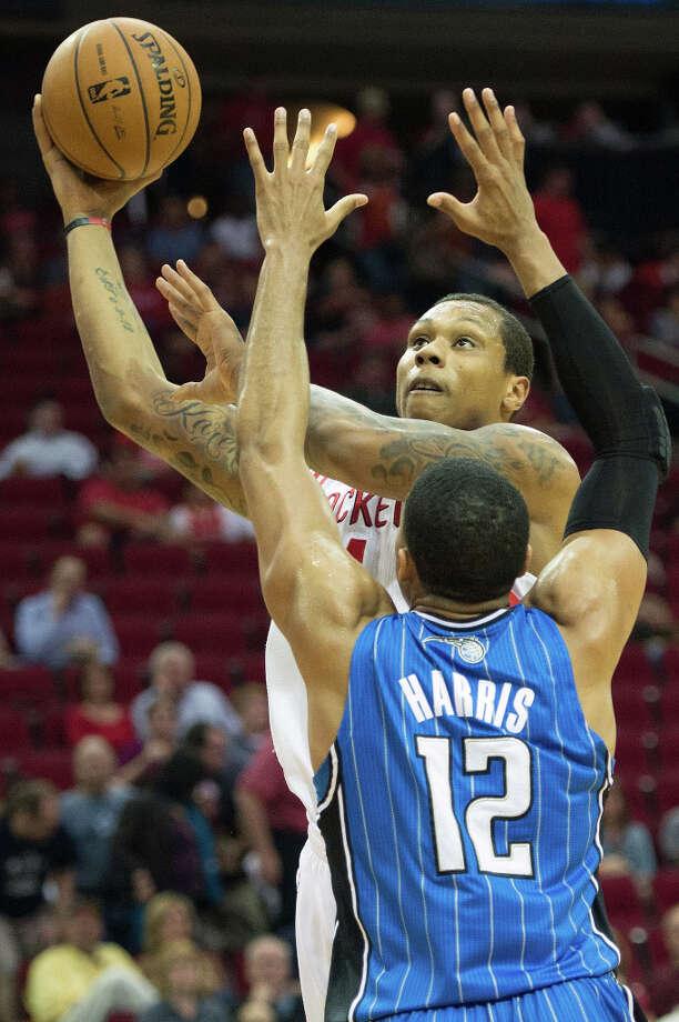 Rockets power forward Greg Smith shoots over Orlando small forward Tobias Harris. Photo: Smiley N. Pool, Houston Chronicle / © 2013  Houston Chronicle