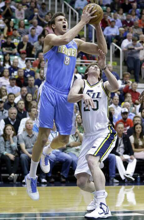 Danilo Gallinari, who led the Nuggets with 21 points, bulls his way past the Jazz's Gordon Hayward. Photo: Rick Bowmer, STF / AP