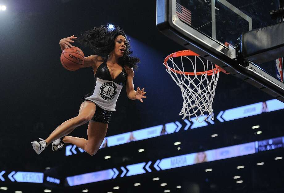 3423 x 2322~~$~~A Brooklyn Nets cheerleader slam dunks a ball during a break while entertaining the crowd during the Nets's game against the Miami Heat during their NBA game at the Barclays Center in the Brooklyn borough of New York City, January 30 , 2013 .  AFP PHOTO/Emmanuel DunandEMMANUEL DUNAND/AFP/Getty Images Photo: EMMANUEL DUNAND