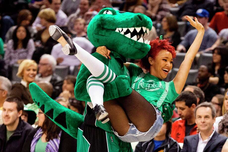 2984 x 1989~~$~~Toronto Raptors mascot, dressed in green to mark St. Patrick's Day, carries a cheerleader off the court during a break in play against the Miami Heat in an NBA basketball game, Sunday, March 17, 2013, in Toronto. Photo: Chris Young