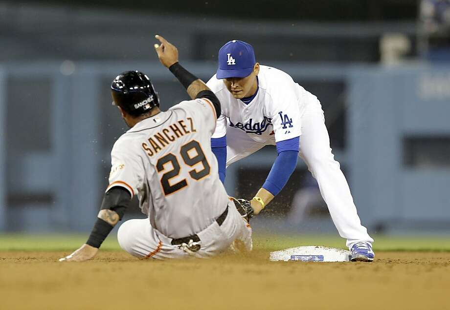 San Francisco Giants' Hector Sanchez is tagged at second by Los Angeles Dodgers shortstop Luis Cruz on a double play in the fourth inning of a baseball game in Los Angeles Wednesday, April 3, 2013. (AP Photo/Reed Saxon) Photo: Reed Saxon, Associated Press