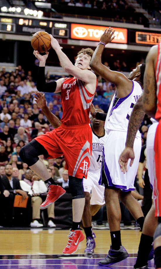 Rockets center Omer Asik drives to the basket against Kings forward Jason Thompson. Photo: Rich Pedroncelli, Associated Press