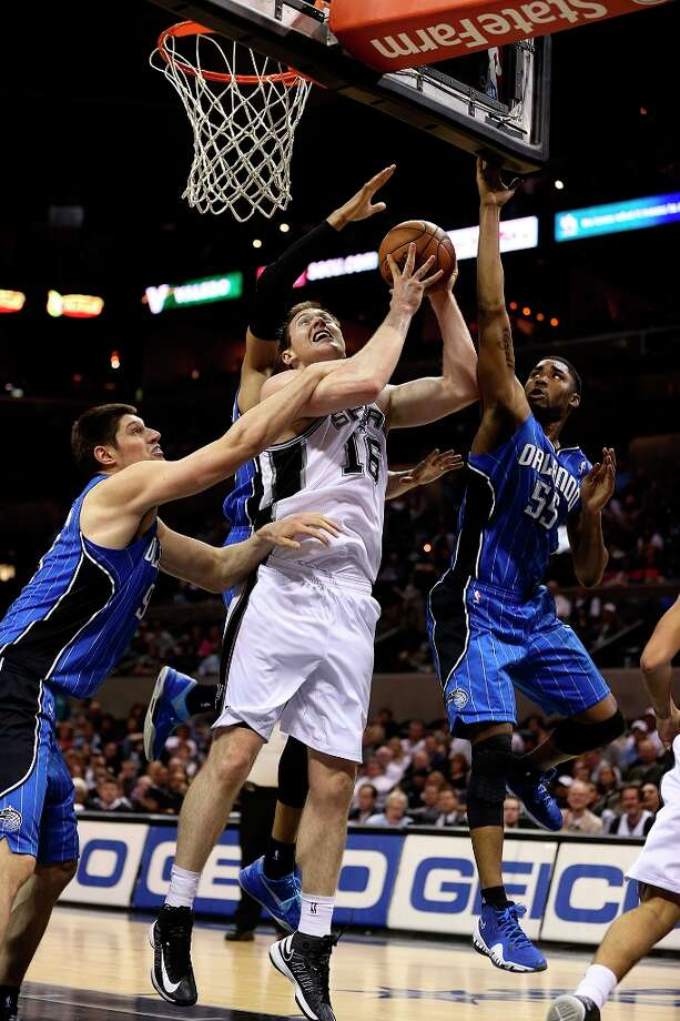 The Spurs\' Aron Baynes is fouled by Orlando Magic\'s Nikola Vucevic (left) as teammate E\'Twaun Moore tries to help during the second half at the AT&T Center, Wednesday, April 3, 3013. The Spurs won 98-84. Photo: Jerry Lara, San Antonio Express-News / ©2013 San Antonio Express-News