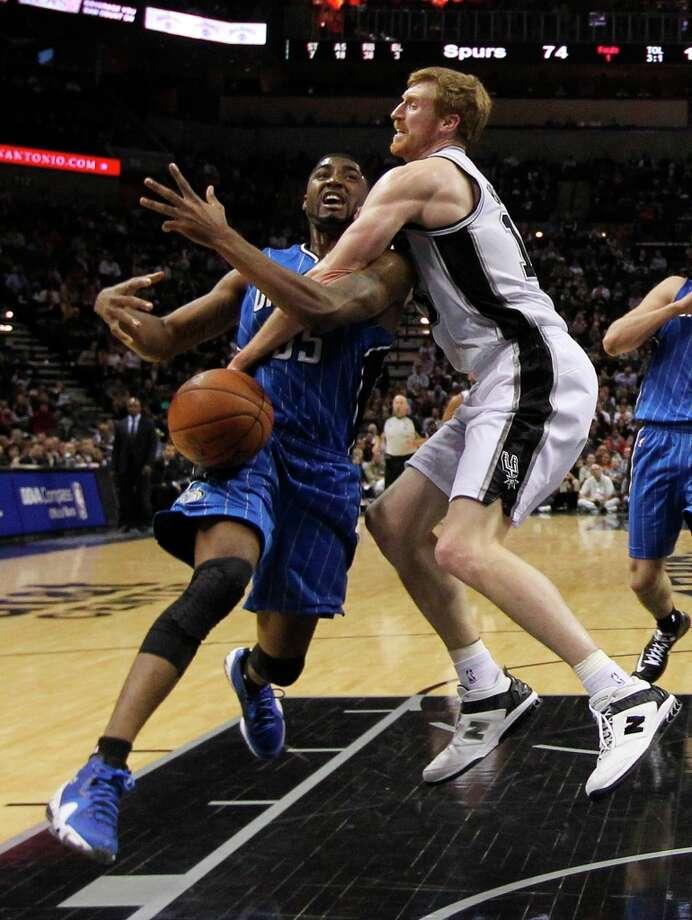 The Spurs\' Matt Bonner ties up Orlando Magic\'s E\'Twaun Moore during the second half at the AT&T Center, Wednesday, April 3, 3013. The Spurs won 98-84. Photo: Jerry Lara, San Antonio Express-News / ©2013 San Antonio Express-News