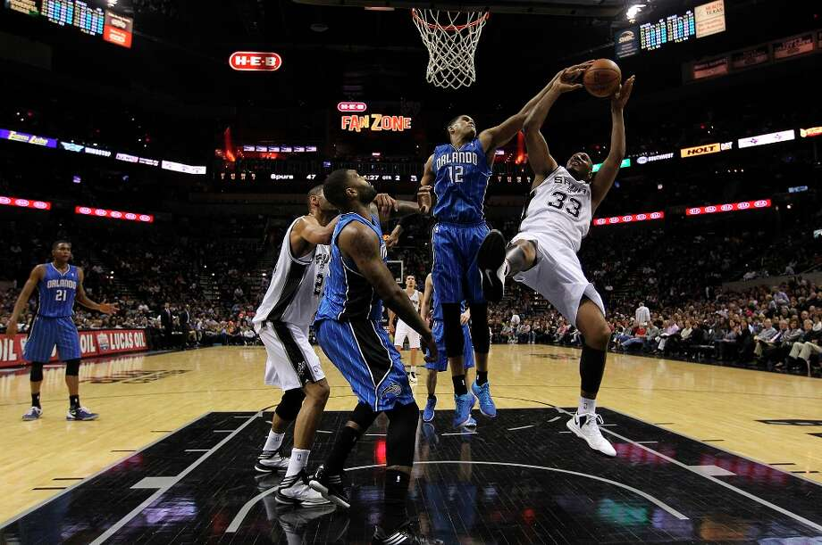 The Spurs\' Boris Diaw is fouled by Orlando Magic\'s Tobias Harris during the first half at the AT&T Center, Wednesday, April 3, 3013. The Spurs won 98-84. Photo: Jerry Lara, San Antonio Express-News / ©2013 San Antonio Express-News