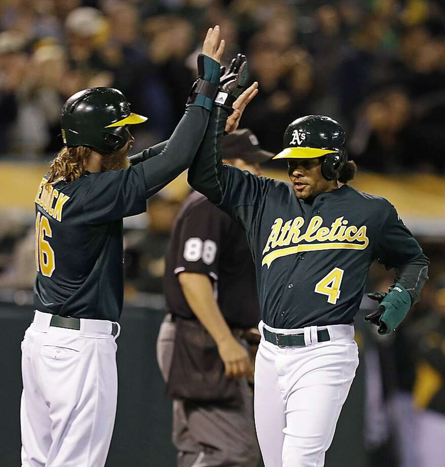 Josh Reddick (left) welcomes Coco Crisp home in the fourth after both scored on Jed Lowrie's double. Photo: Ben Margot, Associated Press