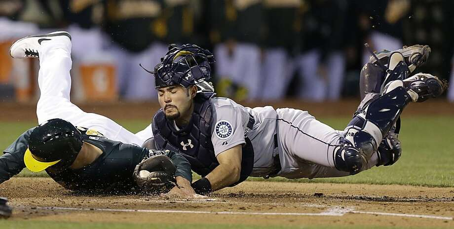 Seattle Mariners catcher Jesus Montero, right, tags out Oakland Athletics' Nate Freiman at home plate in the second inning of a baseball game on Wednesday, April 3, 2013, in Oakland, Calif. Freiman was attempting to score on a double by Scott Sizemore. (AP Photo/Ben Margot) Photo: Ben Margot, Associated Press
