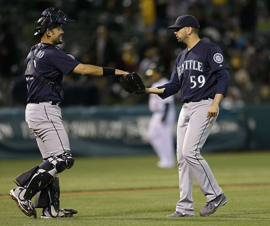 Seattle Mariners' Oliver Perez, right, is congratulated by catcher Jesus Montero at the end of a baseball game against the Oakland Athletics Tuesday, April 2, 2013, in Oakland, Calif. The Mariners won, 7-1. (AP Photo/Ben Margot) Photo: Ben Margot, Associated Press