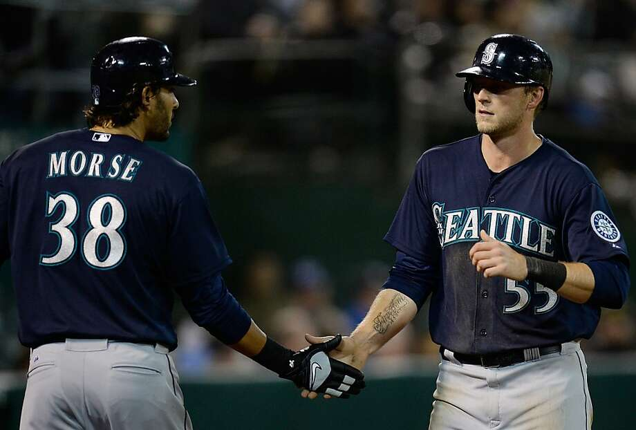 OAKLAND, CA - APRIL 02:  Michael Saunders #55 of the Seattle Mariners is congratulated by Michael Morse #38 after Saunders scored on an RBI double from Kyle Seager #15 (not pictured) against the Oakland Athletics in the eighth inning at O.co Coliseum on April 2, 2013 in Oakland, California. The Mariners won the game 7-1. (Photo by Thearon W. Henderson/Getty Images) Photo: Thearon W. Henderson, Getty Images