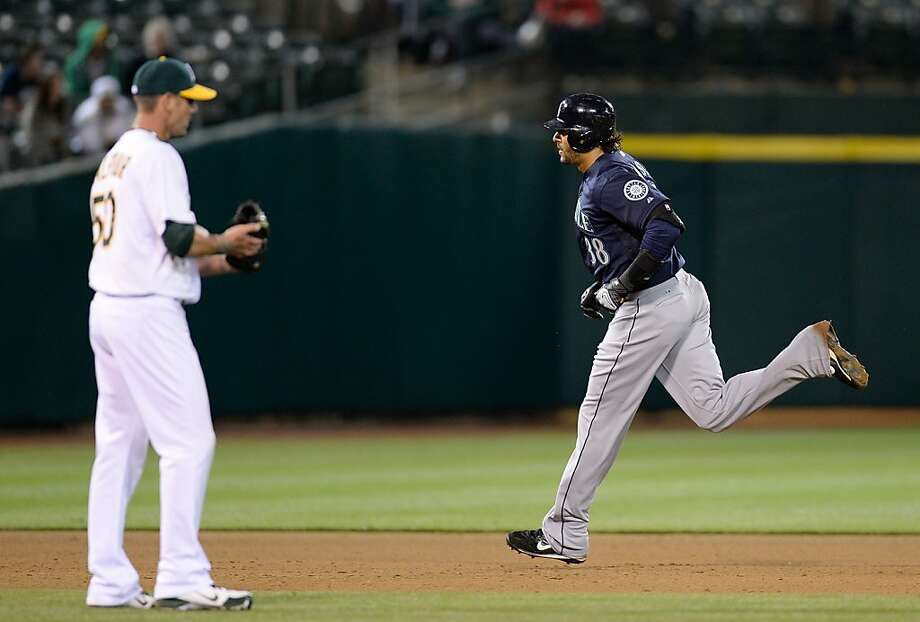 OAKLAND, CA - APRIL 02:  Michael Morse #38 of the Seattle Mariners trots around the bases after hitting his second home run of the game as pitcher Grant Balfour #50 of the Oakland Athletics looks on in the ninth inning at O.co Coliseum on April 2, 2013 in Oakland, California. The Mariners won the game 7-1. (Photo by Thearon W. Henderson/Getty Images) Photo: Thearon W. Henderson, Getty Images