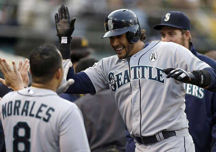 Seattle Mariners' Michael Morse, right, celebrates with Kendrys Morales (8) after Morse hit a home run off Oakland Athletics' Tommy Milone in the first inning of a baseball game on Wednesday, April 3, 2013, in Oakland, Calif. (AP Photo/Ben Margot) Photo: Ben Margot, Associated Press