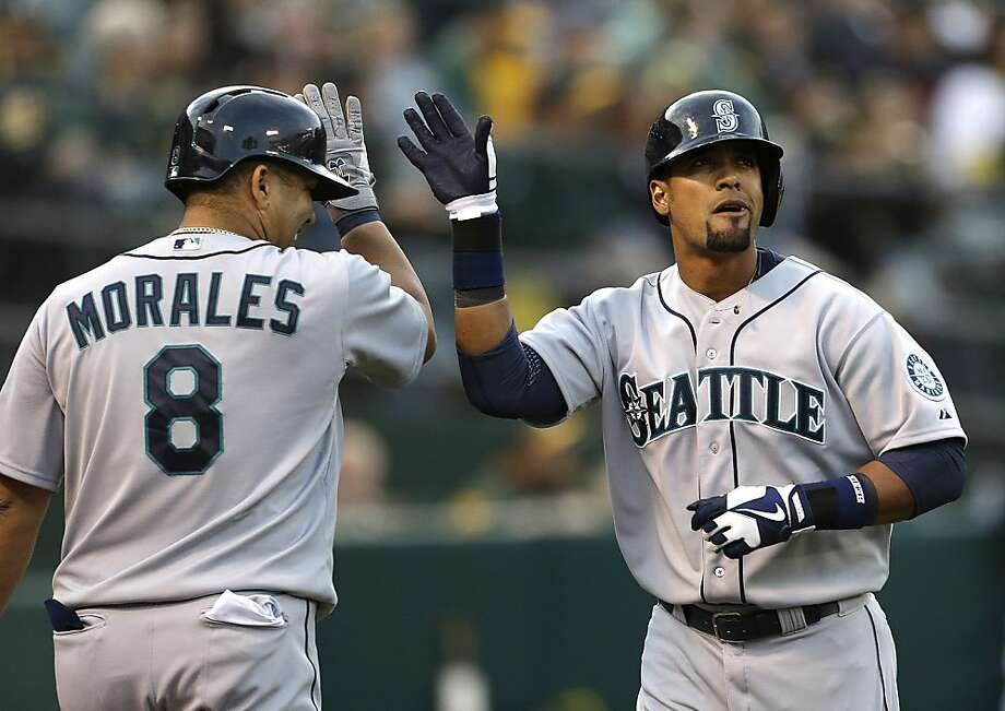 Seattle Mariners' Franklin Gutierrez, right, is congratulated by Kendrys Morales (8) after Gutierrez hit a home run off Oakland Athletics' Tommy Milone in the first inning of a baseball game Wednesday, April 3, 2013, in Oakland, Calif. (AP Photo/Ben Margot) Photo: Ben Margot, Associated Press