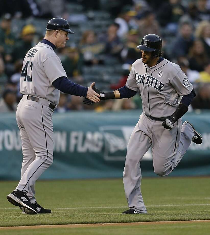 Seattle Mariners' Michael Morse, right, is congratulated by third base coach Jeff Datz after hitting a home run off Oakland Athletics' Tommy Milone in the first inning of a baseball game Wednesday, April 3, 2013, in Oakland, Calif. (AP Photo/Ben Margot) Photo: Ben Margot, Associated Press