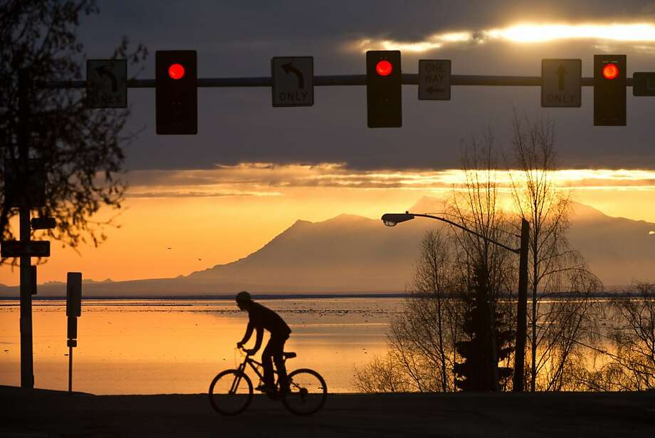 Riding the 'L': A bicyclist heads south on L Street in downtown Anchorage as the late-day sun peeks through the clouds over Cook Inlet. Photo: Marc Lester, Associated Press