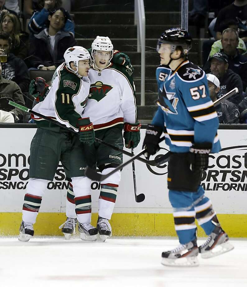 Minnesota Wild's Charlie Coyle, center, celebrates his goal with teammate Zach Parise (11) as San Jose Sharks' Tommy Wingels (57) skates past during the second period of an NHL hockey game in San Jose, Calif., Wednesday, April 3, 2013. (AP Photo/Marcio Jose Sanchez) Photo: Marcio Jose Sanchez, Associated Press
