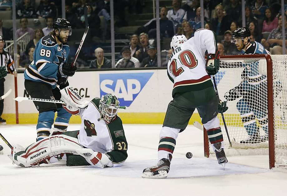 Minnesota Wild's Ryan Suter (20) clears the puck near the goal next to goalie Niklas Backstrom, center, of Finland, and San Jose Sharks' Brent Burns (88) during the first period of an NHL hockey game in San Jose, Calif., Wednesday, April 3, 2013. (AP Photo/Marcio Jose Sanchez) Photo: Marcio Jose Sanchez, Associated Press