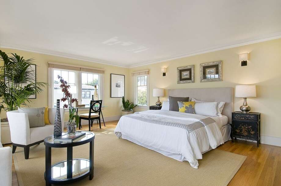 The master suite is elegant with wood floors and light-colored walls.