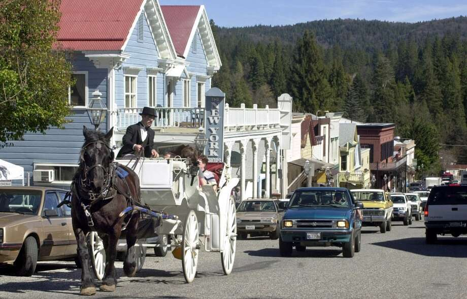 NEVADA CITY: Old and new cross paths as cars follow behind a horse drawn carriage tour through Nevada City.  (Drive time: 2.5 hours) Photo: RICH PEDRONCELLI, ASSOCIATED PRESS / AP2002