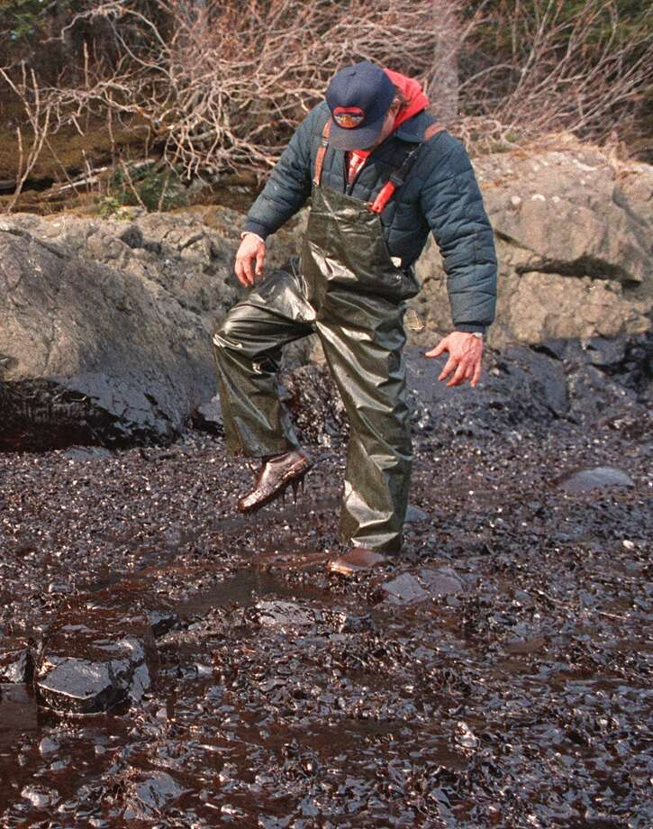 An animal rescue worker finds it sticky going along the shore of Prince William Sound, Alaska,  April 15, 1989, after the oil tanker Exxon Valdez ran aground, spilling some 11 million gallons of crude oil that fouled the shoreline and created an environmental disaster. (AP Photo/John Gaps III) Photo: JOHN GAPS III, AP