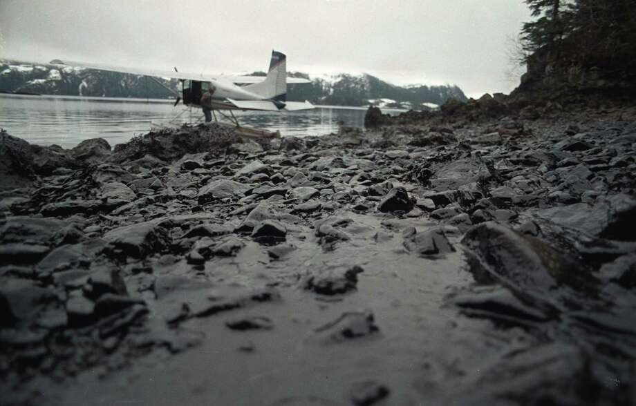 "A float plane waits to taxi from an oil-covered beach in Prince William Sound, an inlet off the Gulf of Alaska in this April 1, 1989 file photo.  A massive oil spill from the tanker ""Exxon Valdez"" has covered more than 100 miles southwest of Valdez. The Supreme Court on Monday agreed to decide whether Exxon Mobil Corp. should pay $2.5 billion in punitive damages in connection with the huge Exxon Valdez oil spill that fouled more than 1,200 miles of Alaskan coastline in 1989. (AP Photo/Jack Smith, File) Photo: Jack Smith, AP"