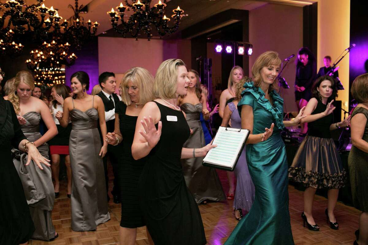 Lauren Peterson, center -- holding clipboard, spends some time on the dance floor at a wedding she planned with her company, Ellanesque.