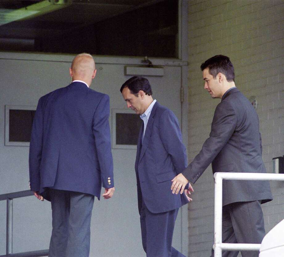 Rex Shelby, center in handcuffs, was the vice president of engineering operations at Enron Broadband. He was one of the last of the Enron employees to be sentenced and pleaded guilty to one count of insider trading and was sentenced to 2 years probation. As of 2011, he was now working in the high-tech industry with pre-Enron colleagues. Photo: Carlos Antonio Rios, Houston Chronicle / Houston Chronicle