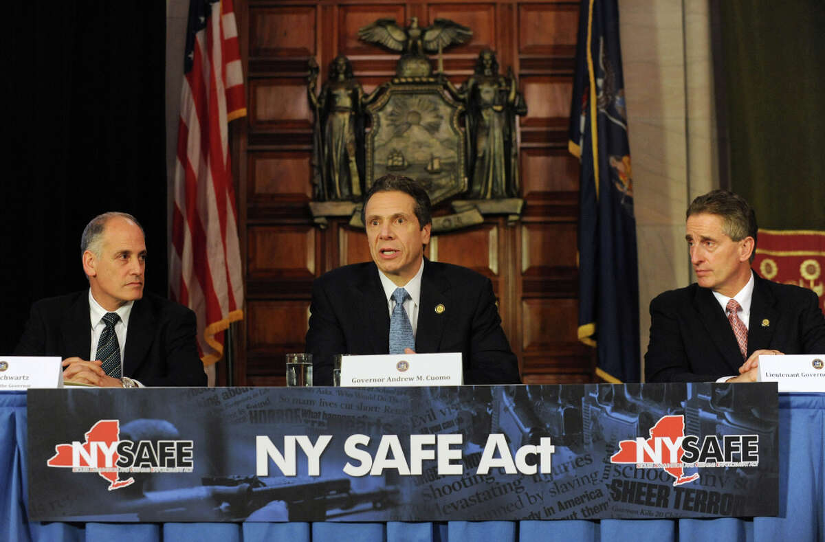 Governor Andrew Cuomo, center, holds a press conference at the Capitol about a bill to broaden the state's definition of banned assault weapons, increase penalties for those convicted of gun crimes and create a statewide registry of assault rifles on Monday Jan. 14, 2013 in Albany, N.Y. Larry Schwartz, Secretary to the Governor, left, and Lt. Gov. Robert Duffy look on at his side. (Lori Van Buren / Times Union)