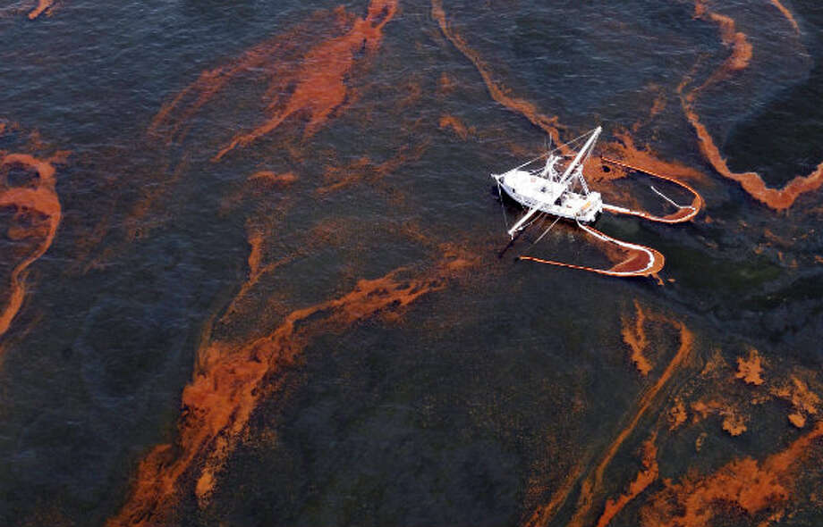 A shrimp boat is used to collect oil with booms in the waters of Chandeleur Sound, La. Photo: Eric Gay/AP