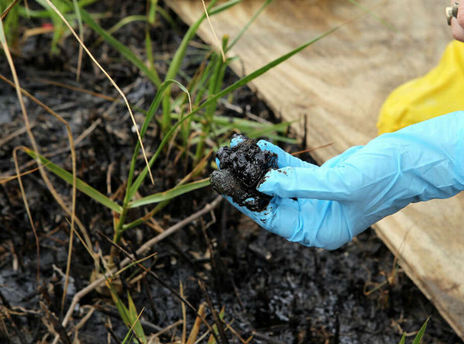 Melanie Driscoll, director of Bird Conservation for the Louisiana Coastal Initiative, holds up oil residue on April 8, 2011. The Louisiana Department of Wildlife & Fisheries gave a press tour to show the effects of the Deepwater Horizon oil spill in Port Sulphur, La. Photo: James Nielsen / Houston Chronicle