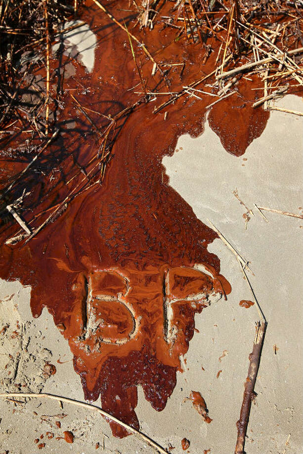 The letters BP, inscribed in sand and oil by a Greenpeace activist, are shown on a beach at the mouth of the Mississippi River on May 17, 2010 near Venice, La. Photo: John Moore/Getty Images