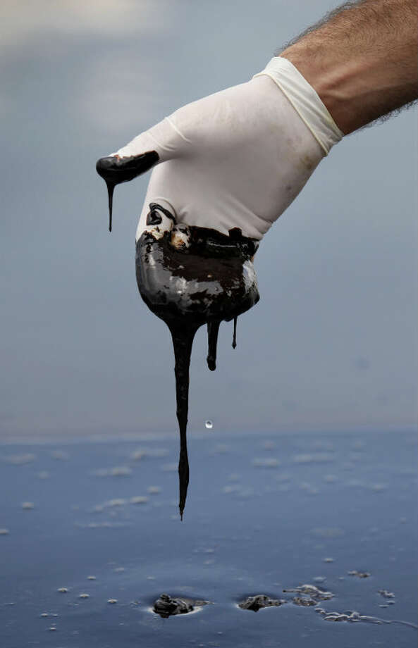 A member of Louisiana Gov. Bobby Jindal's staff reaches into thick oil on the surface of the northern regions of Barataria Bay in Plaquemines Parish, La. on June 15, 2010. Photo: Gerald Herbert/AP