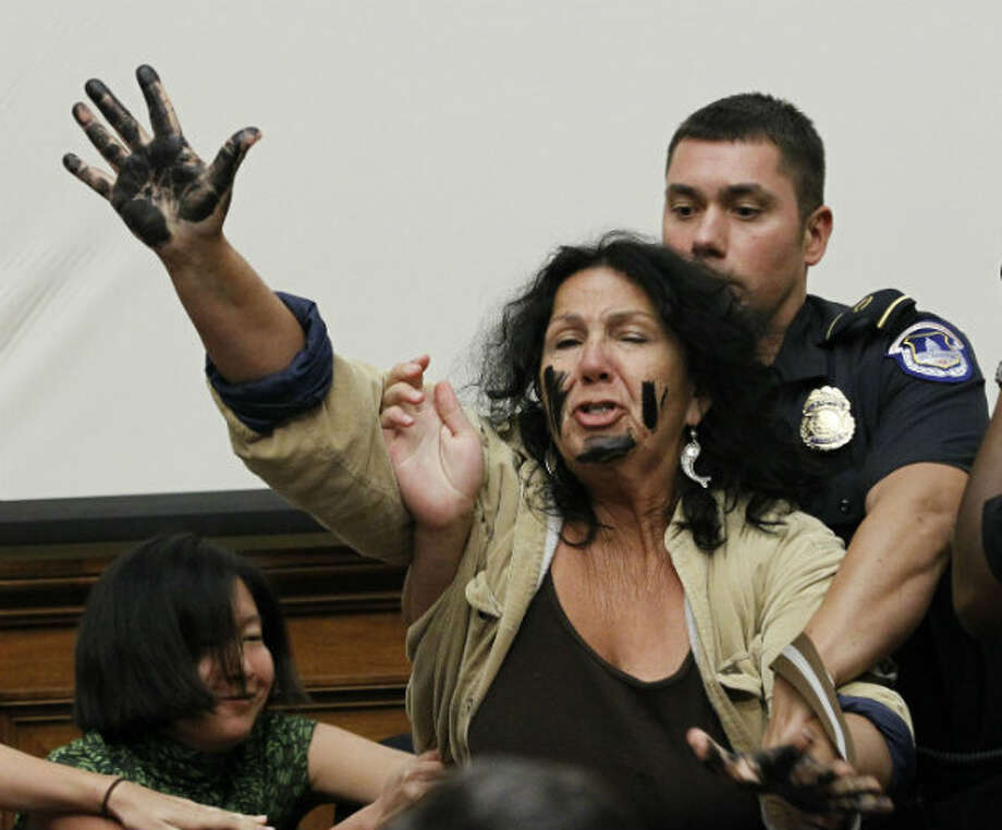 A Capitol Hill police officer arrests Diane Wilson on Capitol Hill in Washington on June 17, 2010. BP CEO Tony Hayward was testifying before the Energy and Environment subcommittee on Oversight and Investigations hearing on the role of BP in the Deepwater Horizon explosion and oil spill. Photo: AP Photo/Haraz N. Ghanbari