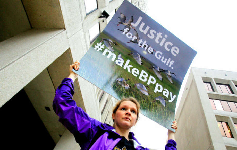 An activist holds a sign during a protest in front of the Hale Boggs Federal Building on the first day of the civil trial over the 2010 Gulf of Mexico oil rig spill on February 25, 2013 in New Orleans, Louisiana. Eleven men were killed during the accident and over 4 million barrels of oil spilled into the Gulf of Mexico in 2010. Photo: Sean Gardner/Getty Images