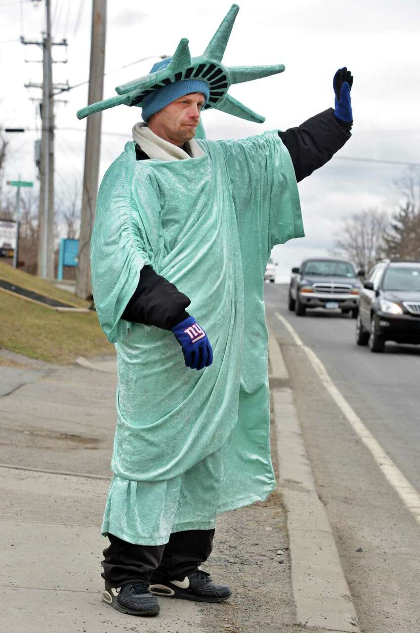 Dressed as the Statue of Liberty, William Coons of Schenectady waves to passing cars outside the Liberty Income Tax office on Altamont Avenue in Schenectady Thursday March 28, 2013. (John Carl D'Annibale / Times Union)