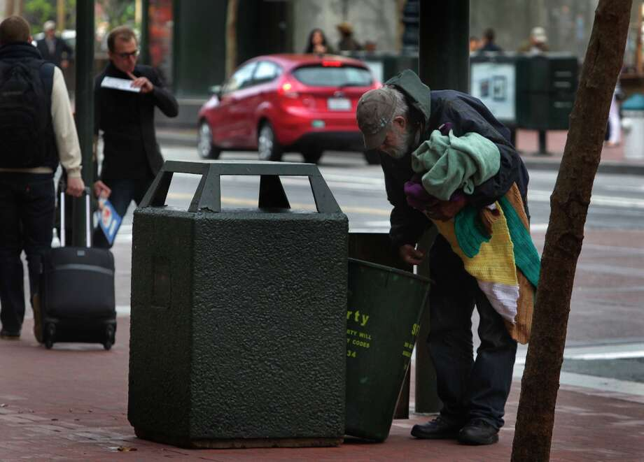 A man rummages through a trash can on Market Street in San Francisco, Calif. on Tuesday, April 2, 2013. City officials say it is too expensive to sort recyclables placed in the public waste canisters. Photo: Paul Chinn, The Chronicle / ONLINE_YES