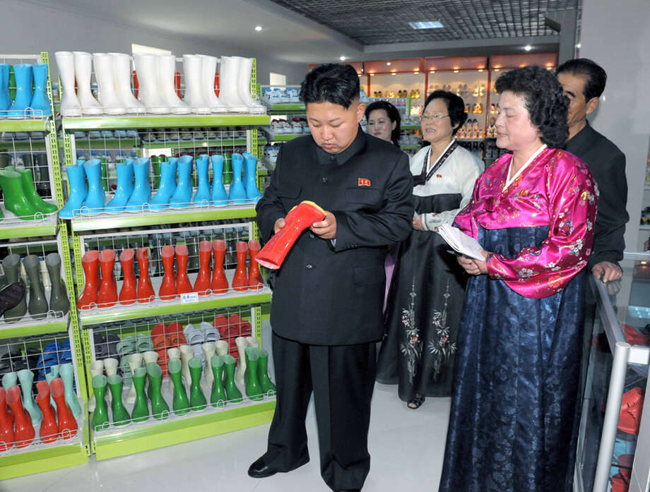 Kim Jong Un looking at miniature rain boots. Photo: Uriminzokkiri's Flickr Stream