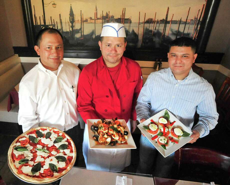 Left to right are Joey Escobar, with a Margherita Pizza; German Escobar, with Zuppa de Pesce; and Jose Caballero, with fresh mozzarella caprese. All three are owners of  Venice Restaurant & Pizza, in Ridgefield, Conn.  Wednesday, April 3, 2013. Photo: Michael Duffy / The News-Times