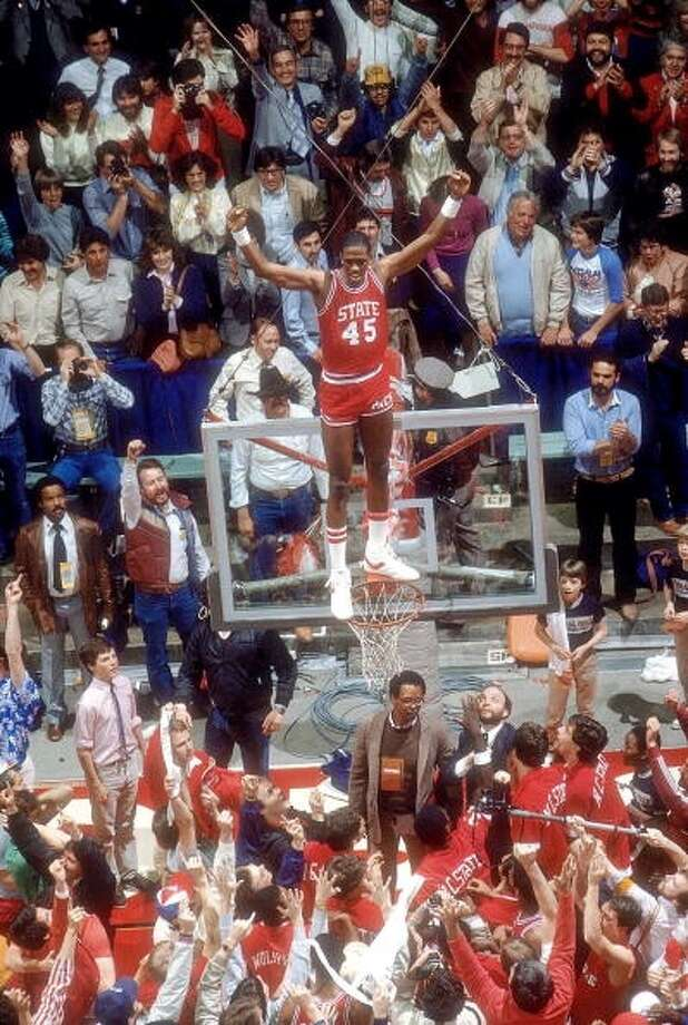 N.C. State's Cozell McQueen stands on the rim after the upset victory.