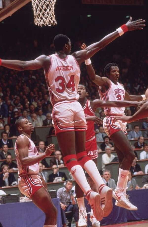 Clyde Drexler and Akeem Olajuwon (34) defend the paint.