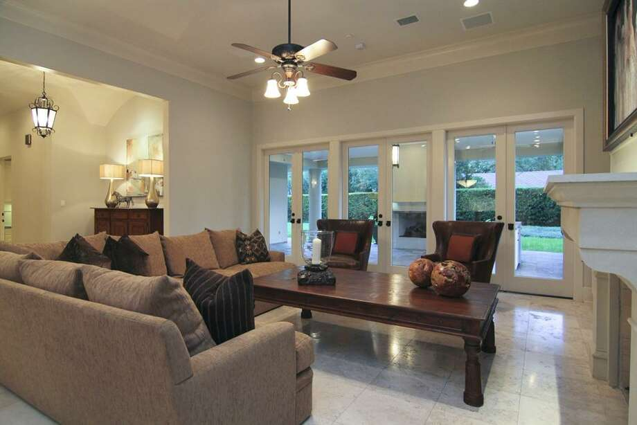 FAMILY ROOM...view looking out to backyard. 3 sets of operable French doors to patio. Stone floors, fireplace, sophisticated AV components. Photo: Martha Turner Properties