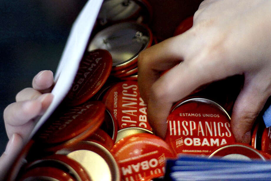 Volunteer Ginny Barahona of Washington, hands out buttons before first lady Michelle Obama spoke at a Hispanic caucus. Photo: David Goldman / AP2012