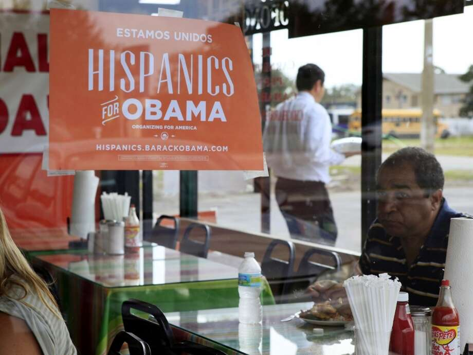 Spanish language election campaign signs promoting President Barack Obama hang on the windows at Lechonera El Barrio Restaurant in Orlando, Fla. on Oct. 26, 2012.