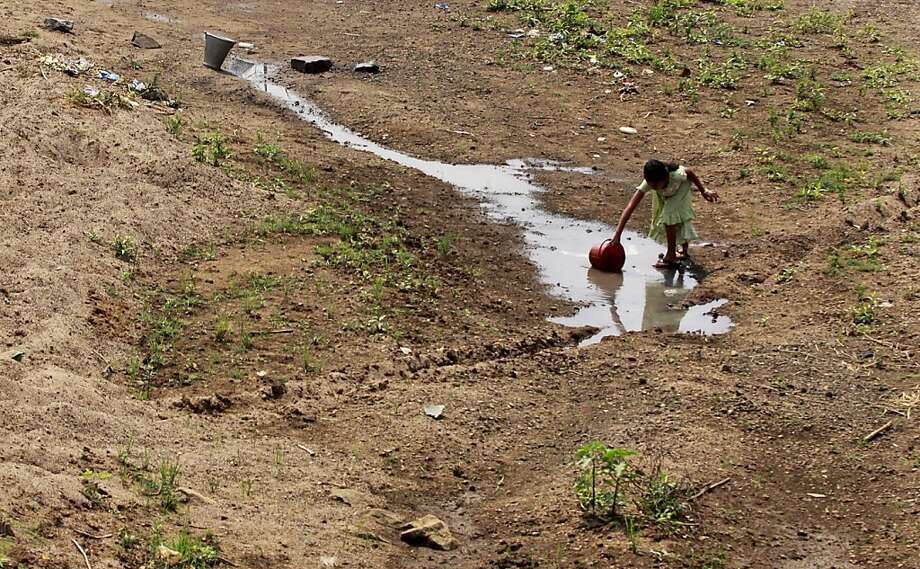 A dead river in a land of drought: A village girl collects water from a puddle in the dried Bada Nadi River near Bhanjanagar, India. The area faces severe water scarcity especially in the summer season. Photo: Biswaranjan Rout, Associated Press